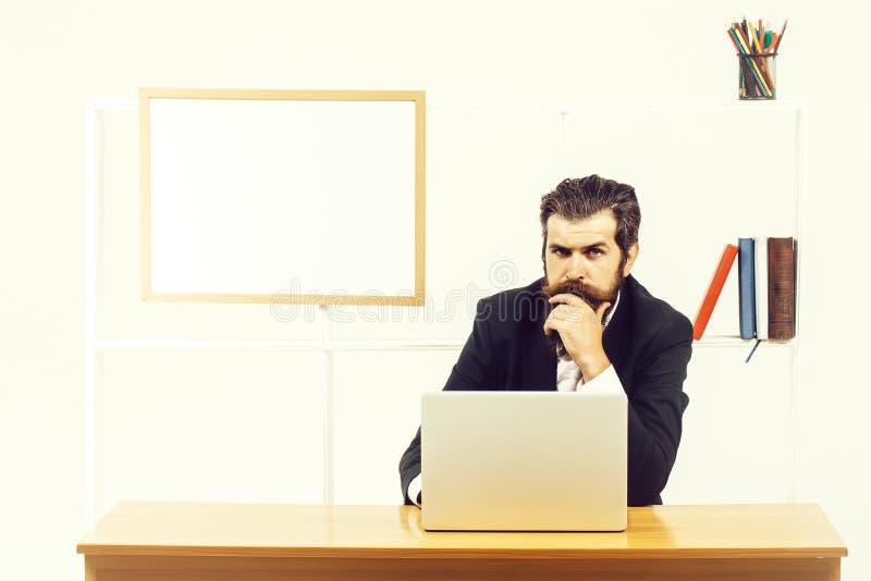 O homem de negócios pensa o assento na mesa fotografia de stock