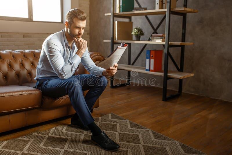 O homem de negócios pensativo considerável novo senta-se no sofá e no jornal lido em seu próprio escritório Levanta Retrato 'sexy fotos de stock royalty free