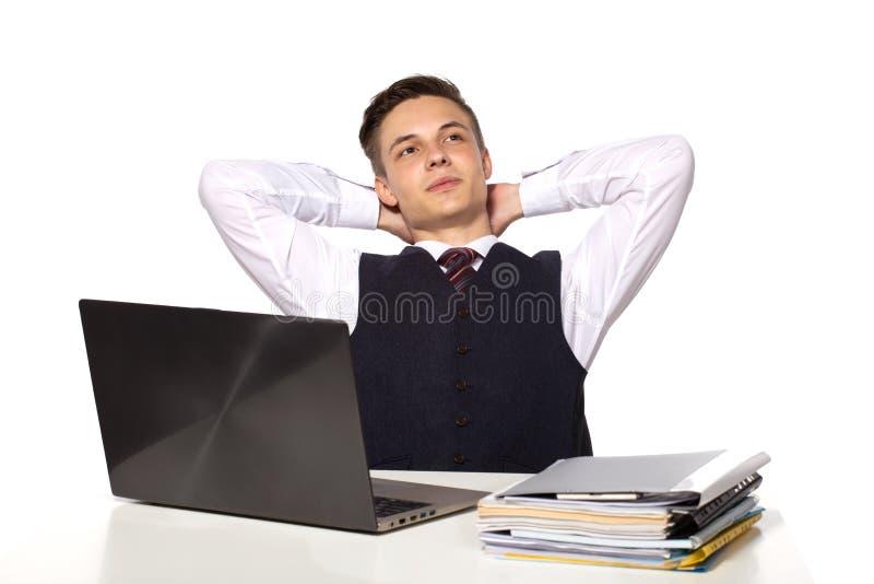 O homem de negócios pensativo novo calcula impostos na mesa no escritório No branco fotografia de stock royalty free