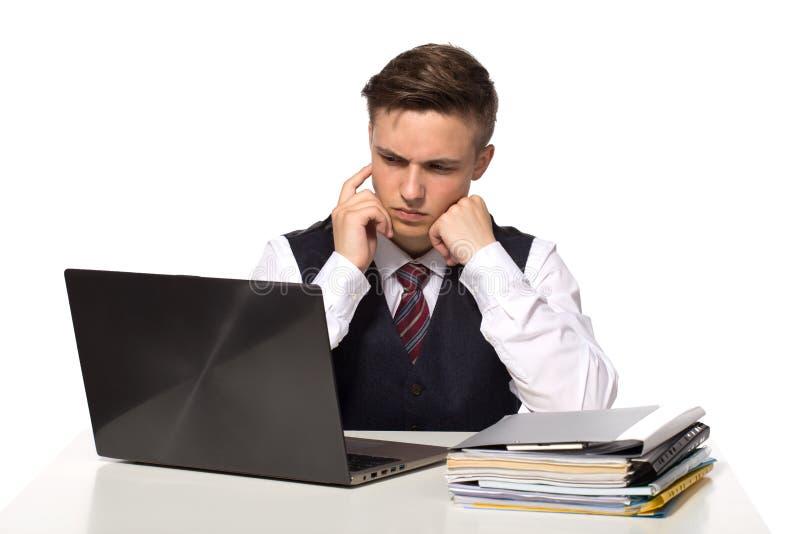 O homem de negócios pensativo novo calcula impostos na mesa no escritório Isolado no branco imagem de stock royalty free