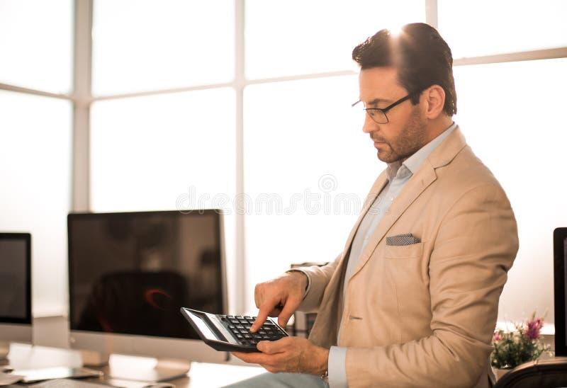 O homem de negócios pode usar a calculadora para calcular o lucro financeiro fotografia de stock royalty free
