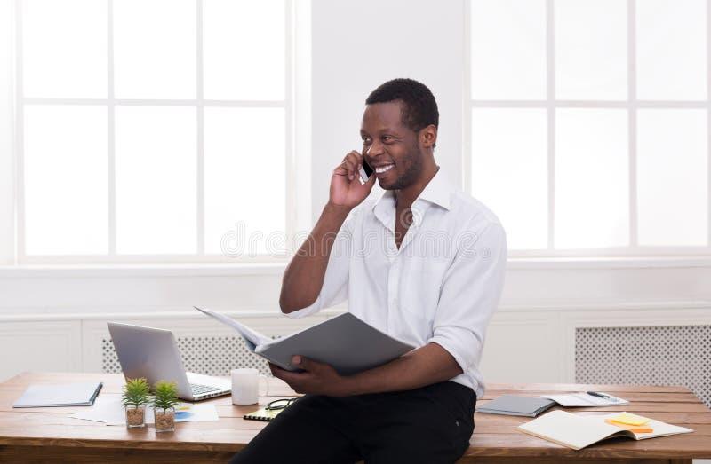 O homem de negócios preto novo leu originais e falou no móbil no escritório branco moderno imagem de stock royalty free
