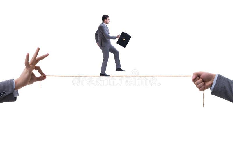 O homem de negócios que anda na corda apertada no conceito do negócio fotografia de stock