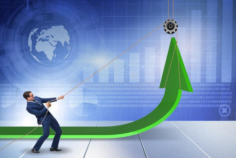 O homem de negócios que apoia o crescimento econômico pela corda puxando imagem de stock