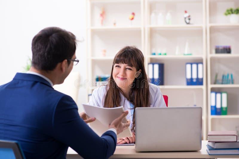 O homem de negócios que discute problemas de saúde com o doutor fotos de stock