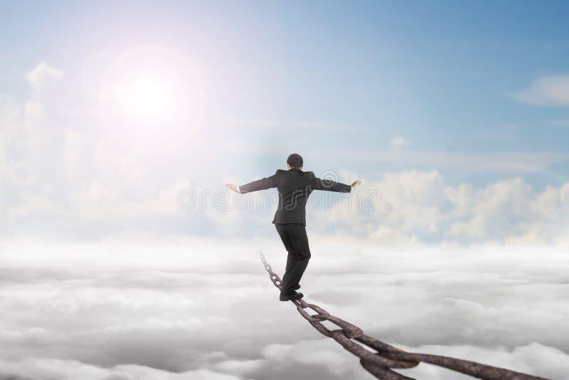 O homem de negócios que equilibra na corrente velha do ferro com luz solar do céu nubla-se imagem de stock royalty free