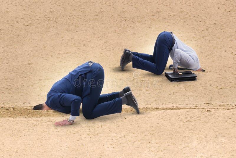 O homem de negócios que esconde sua cabeça na areia que escapa dos problemas imagens de stock royalty free