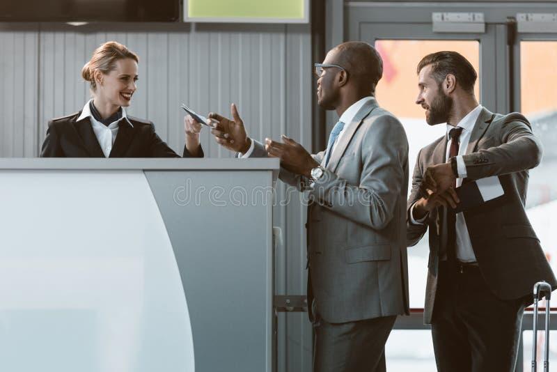 o homem de negócios que está no aeroporto verifica dentro o contador, apressa-se acima imagem de stock