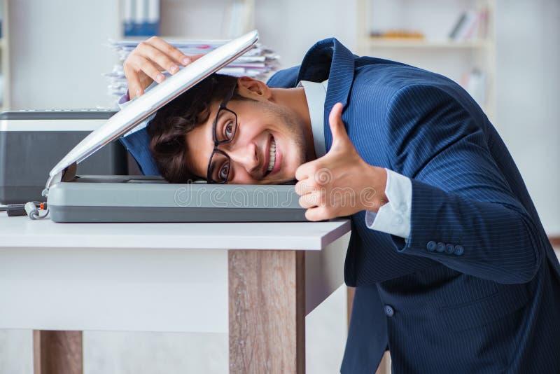 O homem de negócios que faz cópias na máquina de copi fotografia de stock