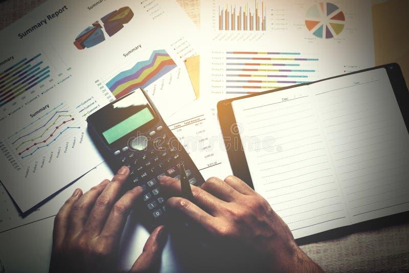 O homem de negócios que faz a finança e calcula na mesa com analyaing s fotografia de stock