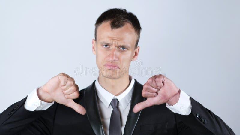 O homem de negócios que faz os polegares gesticula para baixo com ambas as mãos imagem de stock royalty free