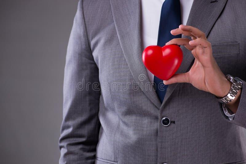O homem de negócios que guarda o coração vermelho no conceito do amor fotografia de stock royalty free