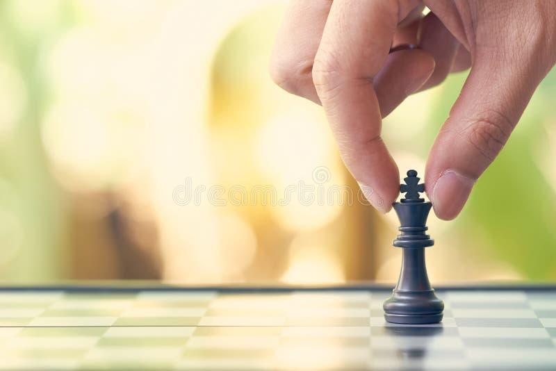 O homem de negócios que guarda um rei Chess é colocado em um tabuleiro de xadrez utilização como o conceito do negócio do fundo e foto de stock royalty free