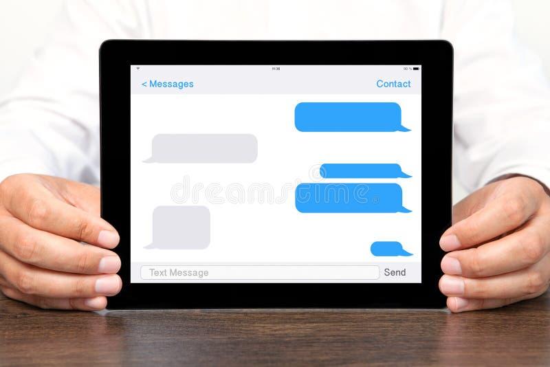 O homem de negócios que guarda um tablet pc com sms conversa em uma tela fotografia de stock