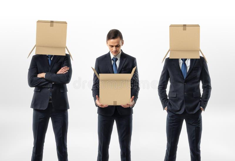 O homem de negócios que guarda uma caixa de cartão aberta, os outros dois está vestindo as caixas em suas cabeças imagens de stock