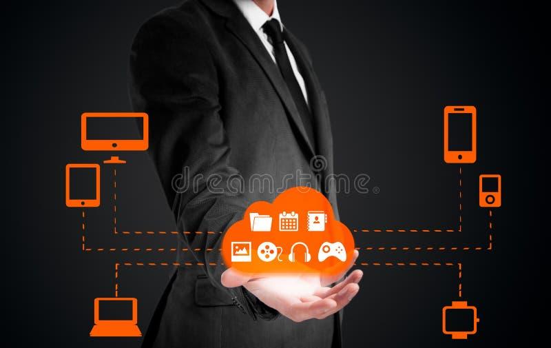 O homem de negócios que guarda uma nuvem conectou a muitos objetos em um conceito da tela virtual sobre o Internet das coisas imagens de stock royalty free