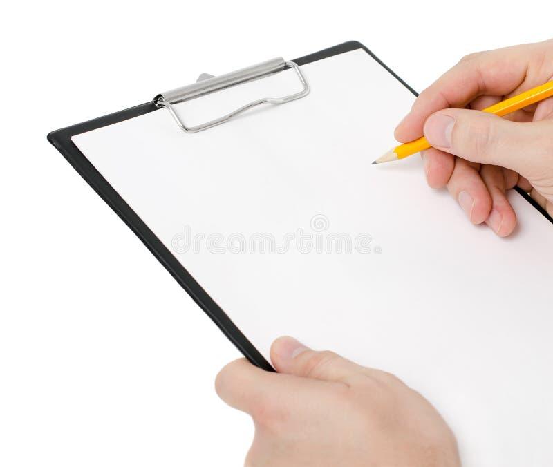 O homem de negócios que guarda uma prancheta e escreve nela imagem de stock