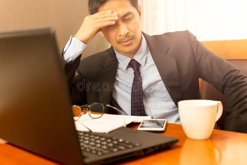 O homem de negócios que inclina-se com mão em sua cabeça nos olhos fechou o sentimento sonolento imagens de stock
