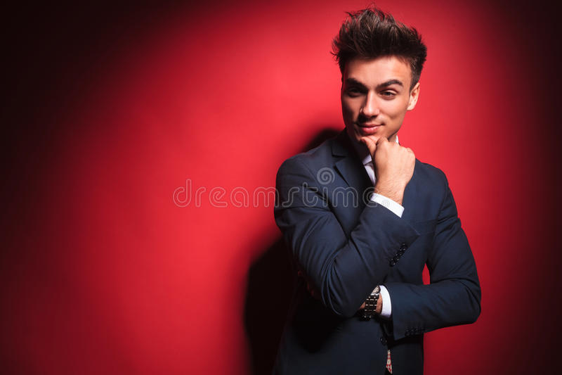 O homem de negócios que pensa com mãos cruzou-se no estúdio vermelho fotografia de stock
