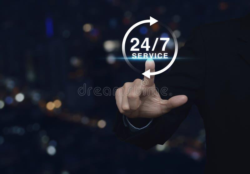 O homem de negócios que pressiona o botão 24 horas presta serviços de manutenção ao ícone sobre o ligh do borrão imagem de stock royalty free
