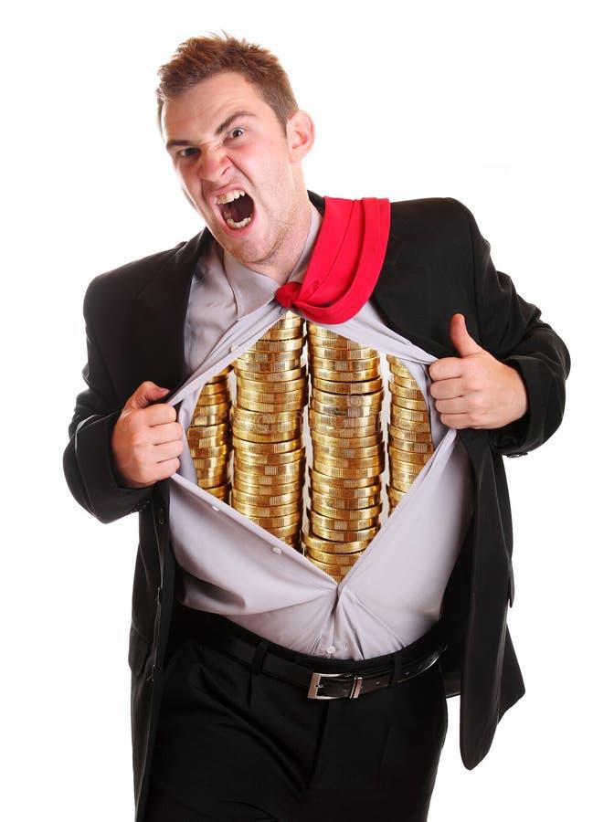 O homem de negócios que rasga sua camisa empilha moedas nela fotografia de stock