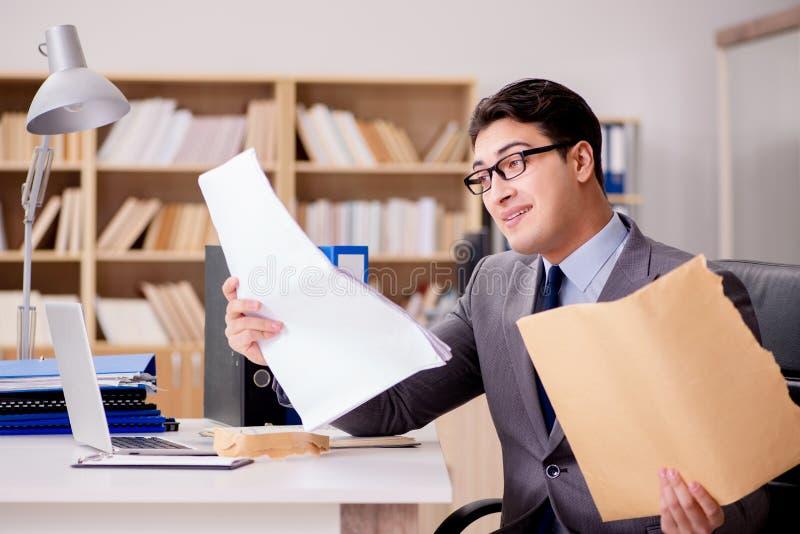 O homem de negócios que recebe o envelope da letra no escritório fotos de stock
