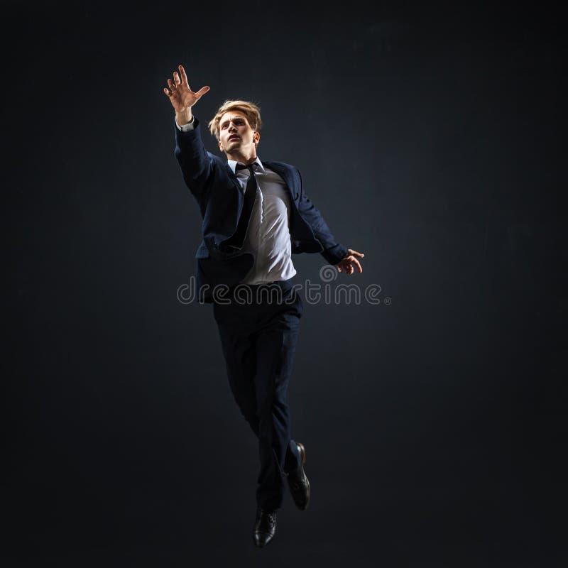 O homem de negócios que salta acima Homem novo em procurar do terno de negócio mais alto fotos de stock royalty free
