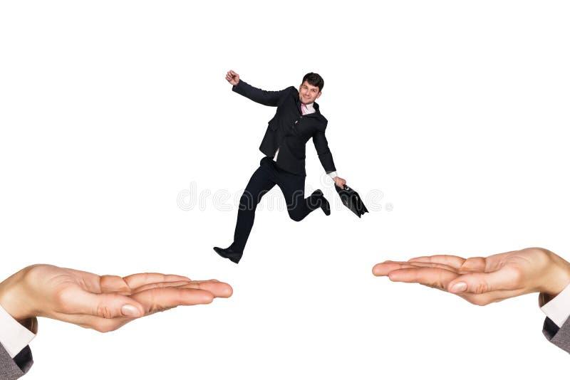 O homem de negócios que salta nas mãos imagem de stock royalty free