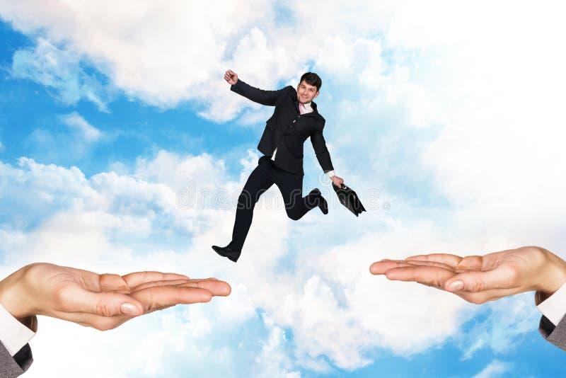 O homem de negócios que salta no céu imagem de stock