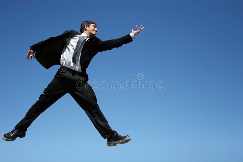 O homem de negócios que salta para o sucesso foto de stock