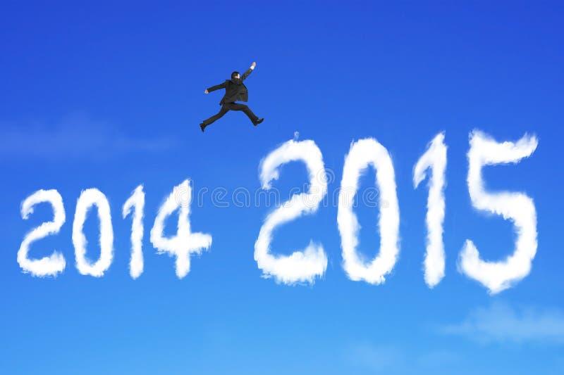 O homem de negócios que salta sobre a nuvem de 2015 formas no céu azul imagens de stock