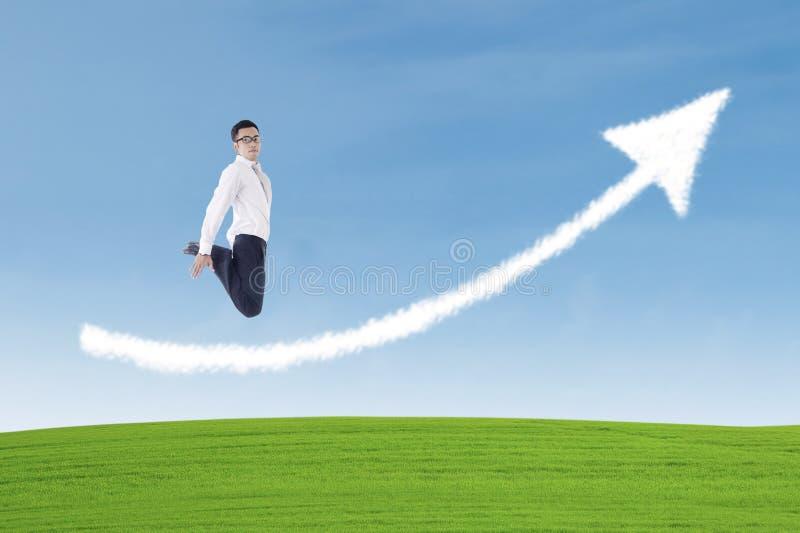 O homem de negócios que salta sobre a nuvem do sinal da seta do sucesso fotografia de stock royalty free