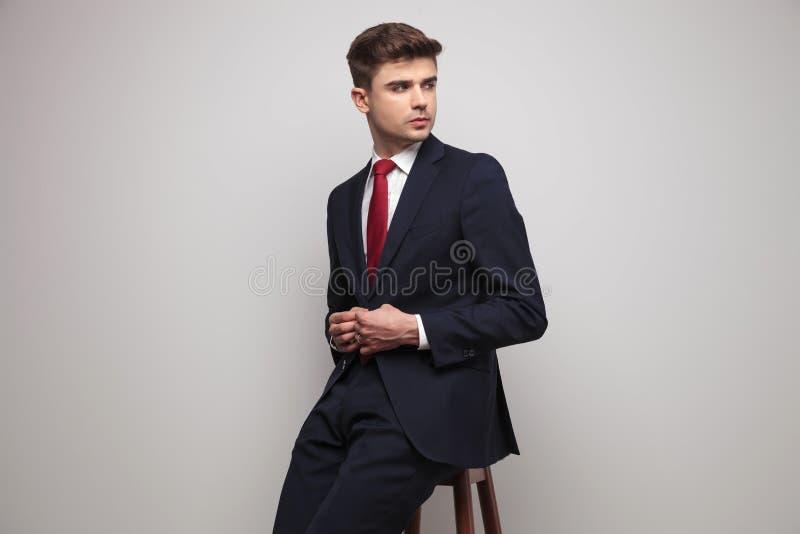 O homem de negócios que senta-se na cadeira desabotoa o terno e olha para tomar partido imagens de stock
