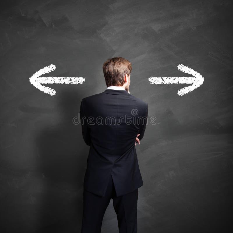 O homem de negócios que tem que decidir que maneira de ir imagem de stock
