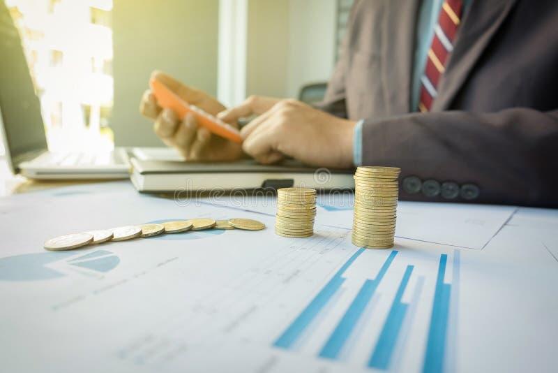 O homem de negócios que usa a calculadora com moedas empilhadas arranjou no offi imagem de stock