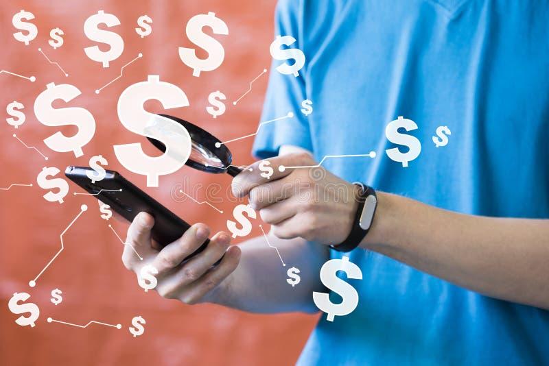 O homem de negócios que usam o telefone esperto móvel e a lupa procuram Olha o balanço de contas da moeda do dólar fotos de stock royalty free