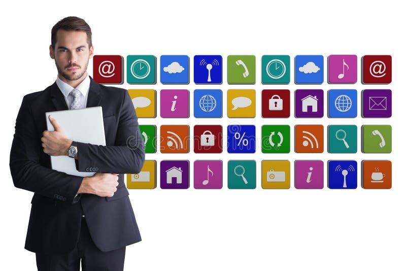 O homem de negócios que veste um terno está mantendo o caderno contra o fundo do ícone da aplicação fotografia de stock