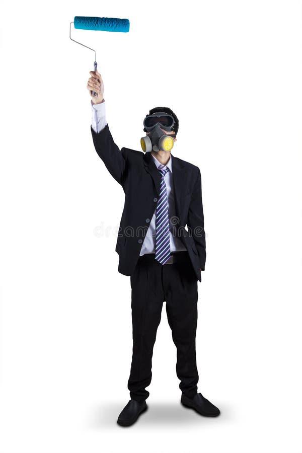 O homem de negócios que veste uma máscara de gás está pronto para pintar fotografia de stock royalty free