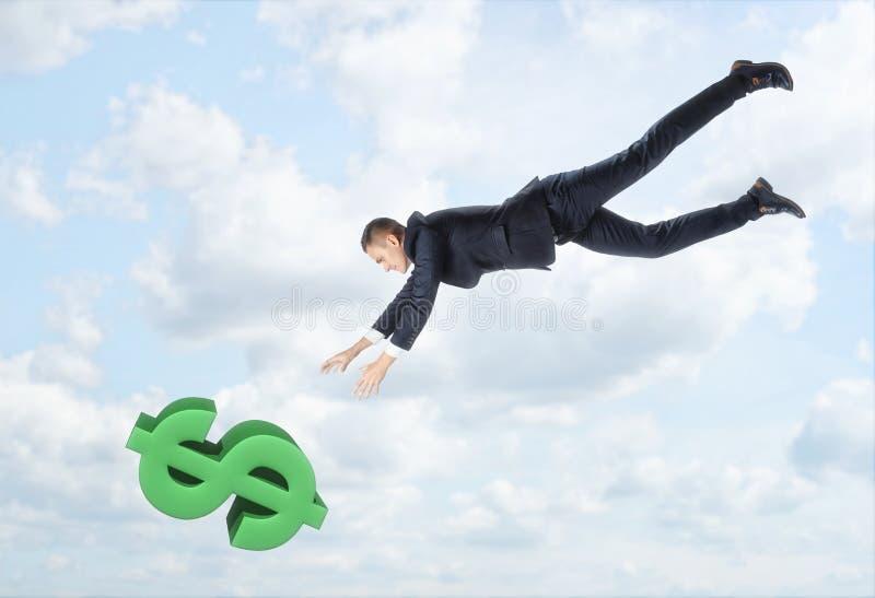 O homem de negócios que voa para baixo ao sinal de dólar grande com o seu entrega outstreched no fundo do céu azul fotos de stock royalty free