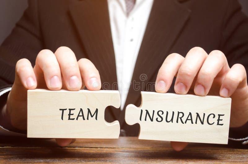 O homem de negócios recolhe enigmas com as palavras Team Insurance Segurança e segurança em uma equipe do negócio Cuidado para em fotos de stock