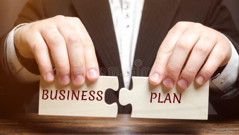 O homem de negócios recolhe enigmas com o plano de negócios da palavra Programa das operações comerciais Organização e gestão dos fotografia de stock