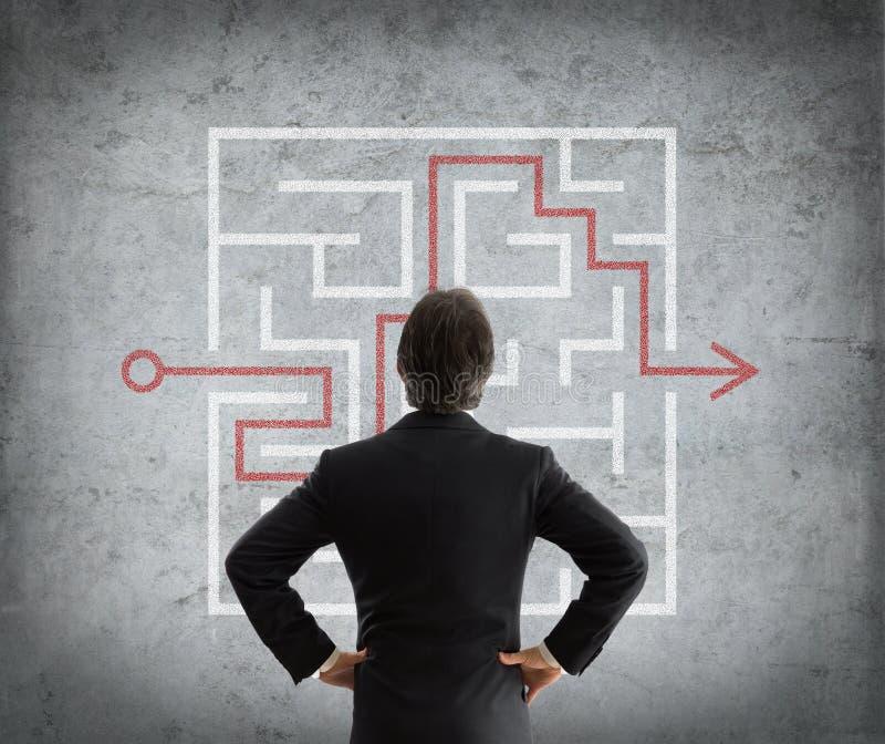 O homem de negócios resolve labirinto complicado imagens de stock