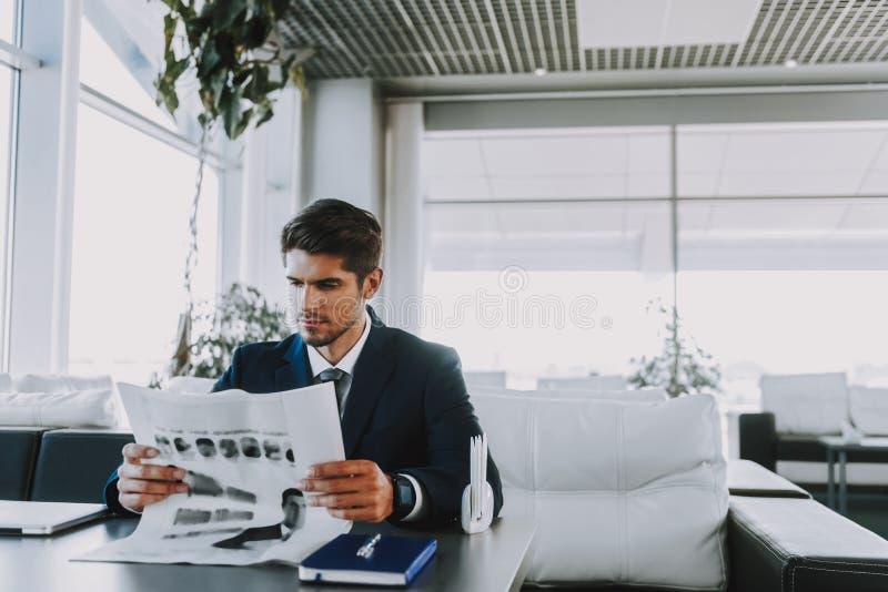 O homem de negócios sério está lendo a notícia no café fotos de stock royalty free