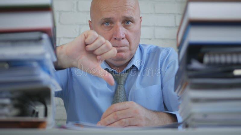 O homem de negócios sério In Office Room faz para não gostar dos polegares abaixo dos gestos de mão foto de stock royalty free