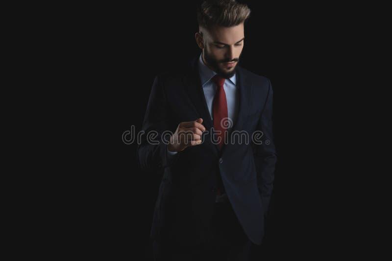 O homem de negócios sedutor que guarda bolsos olha para baixo para tomar partido foto de stock