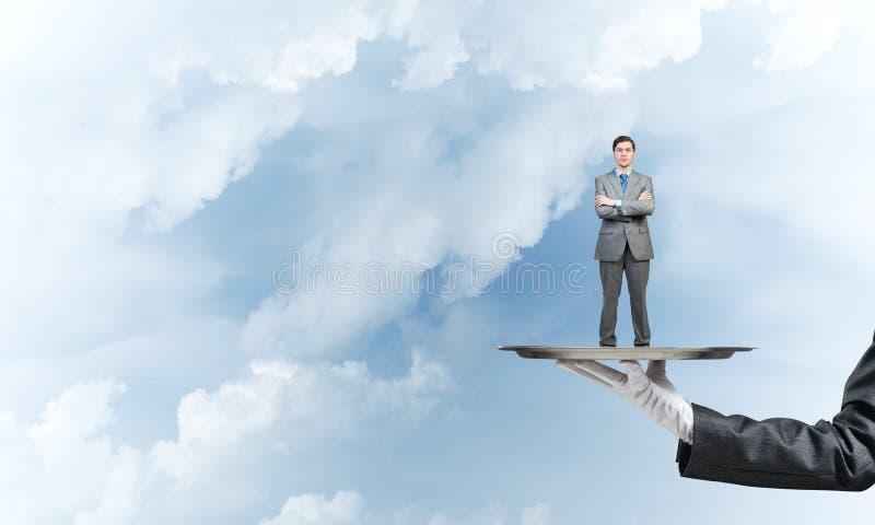 O homem de negócios seguro apresentou na bandeja do metal contra o fundo do céu azul imagem de stock royalty free