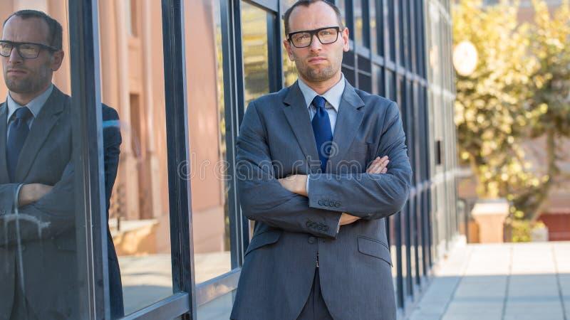 O homem de negócios seguro com braços cruzou-se ao lado de sua construção do escritório imagens de stock royalty free