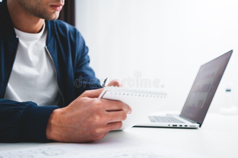 O homem de negócios senta-se em sua mesa e projeto da preparação imagens de stock royalty free
