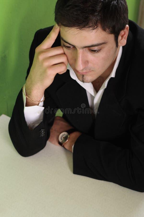 O homem de negócios senta-se em uma tabela fotografia de stock royalty free