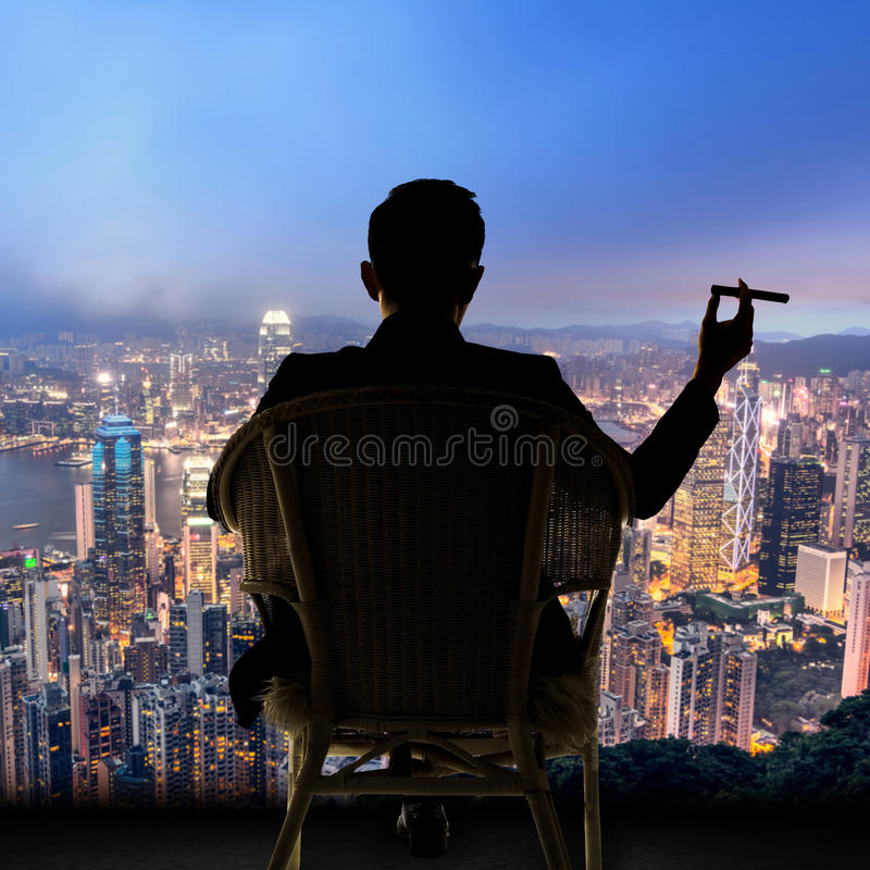 O homem de negócios senta-se na cadeira imagem de stock royalty free